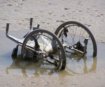 A wheelchair semi-submerged in a muddy puddle