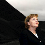 Angela Merkel beside a coal mountain